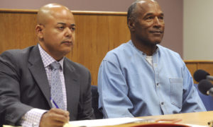 Former NFL football star O.J. Simpson appears with his attorney, Malcolm LaVergne, left, via video for his parole hearing at the Lovelock Correctional Center in Lovelock, Nev., on Thursday, July 20, 2017. Simpson was convicted in 2008 of enlisting some men he barely knew, including two who had guns, to retrieve from two sports collectibles sellers some items that Simpson said were stolen from him a decade earlier. (Jason Bean/The Reno Gazette-Journal via AP, Pool) ORG XMIT: NVREN404
